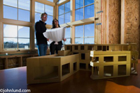 People looking at blueprints with building model in foreground. Two people, a man and a woman, presumably architects, are holding a set of blue prints and looking up at the office building interior.